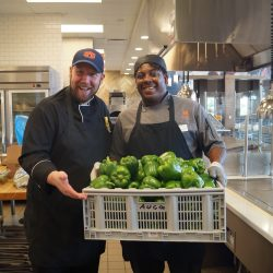 Two Tiger Dining chefs smiling and holding a crate of green bell peppers in Wellness Kitchen..