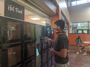 Student using temperature-controlled food locker system at Foy
